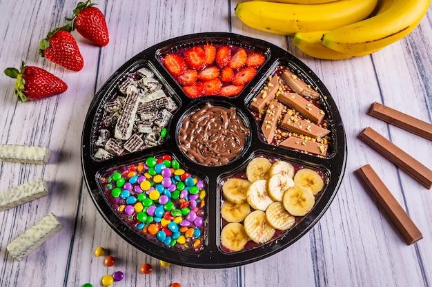 Acai mrożone z bananem, granolą, czekoladą i cukierkami na podzielenie.