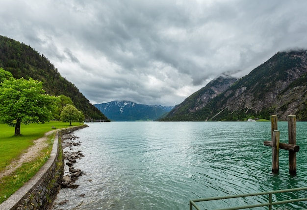 Achensee (jezioro achen) letni krajobraz z zieloną łąką i drewnianym cumowaniem (austria)
