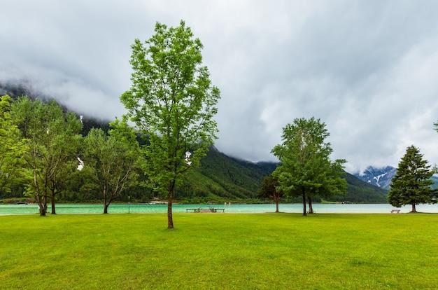 Achensee (jezioro achen) letni krajobraz z zieloną łąką i drewnianymi miejscami do cumowania (austria).