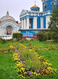 Achinsk, syberia, rosja -09.01.2021: kwiatowy trawnik na tle portyku wejściowego cerkwi