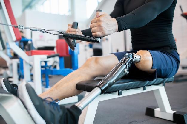 Adaptacyjny atleta używa wioślarskiej maszyny zbliżenie