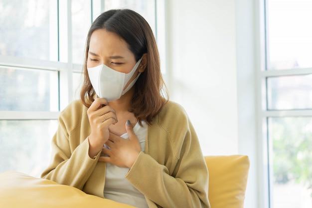 Addle kobieta nosi maskę na twarz, kaszle i dotyka klatki piersiowej, aby sprawdzić, czy płuca nie chroni koronawirus