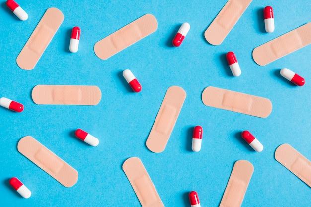 Adhesive bandaże i kapsuły na błękitnym tle