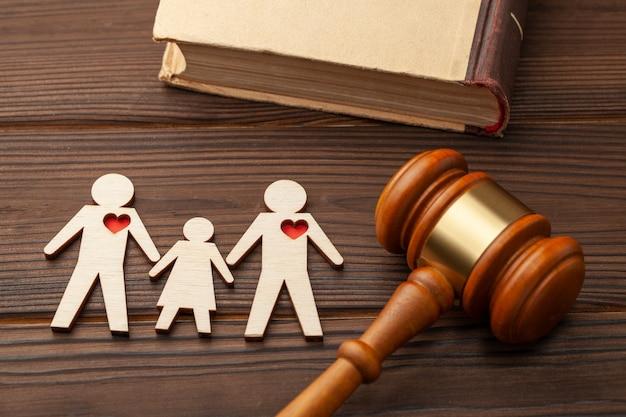 Adopcja dziecka przez parę osób tej samej płci. młotek sędziego i postacie dwóch gejów z dzieckiem trzymają się za ręce.