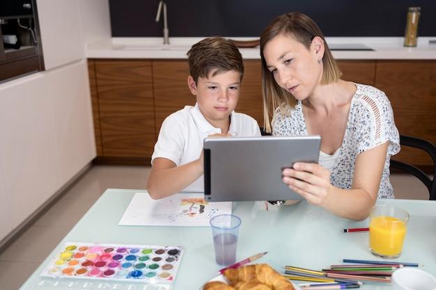 Adorable młody chłopak sprawdza tablet z matką