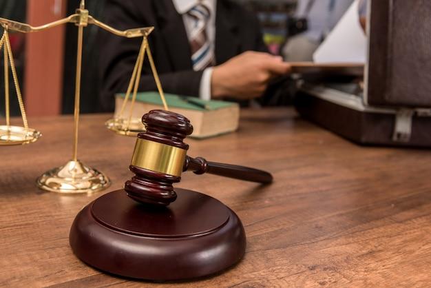 Adwokat trybunału pracuje z dokumentami i drewnianym młotkiem na stole w sali sądowej.