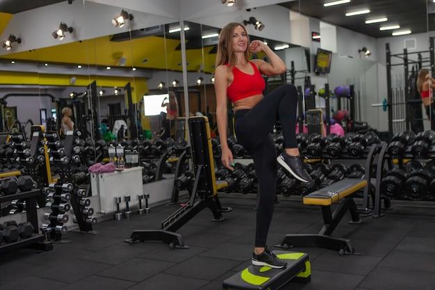 Aerobik. kobieta o szczupłej sylwetce ćwicząca wchodzenie na platformę schodową w nowoczesnej siłowni