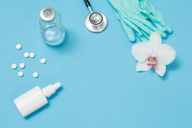 Aerozol do nosa, pigułki, szklany termometr rtęciowy, fonendoskop i rękawice nitrylowe do ochrony osobistej. widok z góry. koncepcja zestawu ochronnego przed wirusami.