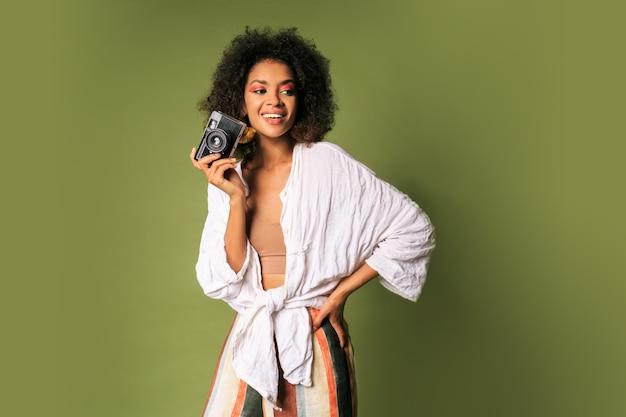 Afican kobieta trzymając aparat fotograficzny retro i śmiejąc się.