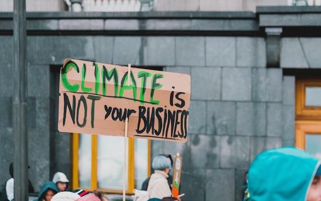 """Afisz """"klimat nie jest twoją sprawą"""" podczas marszu przeciwko zanieczyszczeniom planety."""