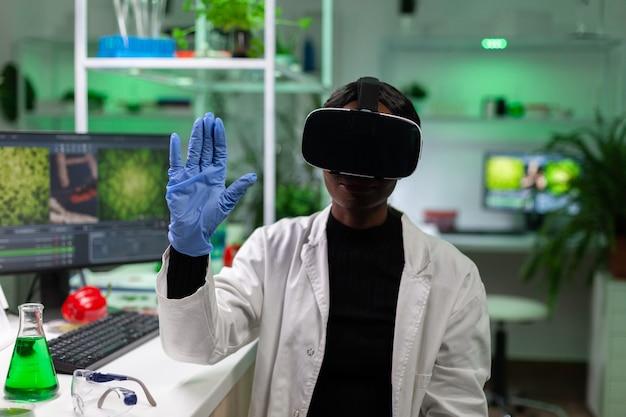 African american biolog kobieta nosząca zestaw wirtualnej rzeczywistości, pracująca w eksperymencie mikrobiologicznym