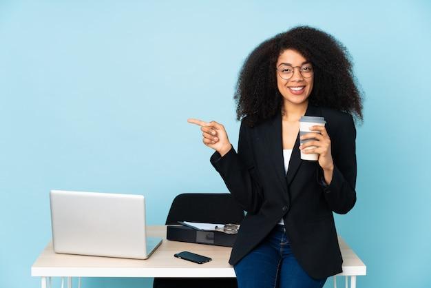 African american biznes kobieta pracująca w swoim miejscu pracy, wskazując palcem na bok