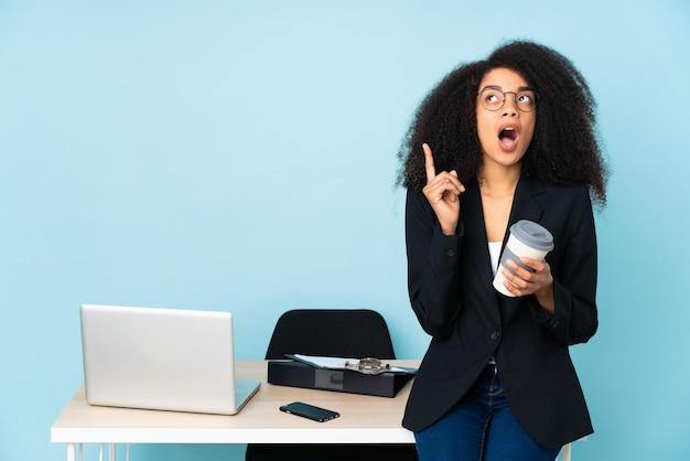 African american biznes kobieta pracuje w swoim miejscu pracy, myśląc pomysł wskazując palcem w górę