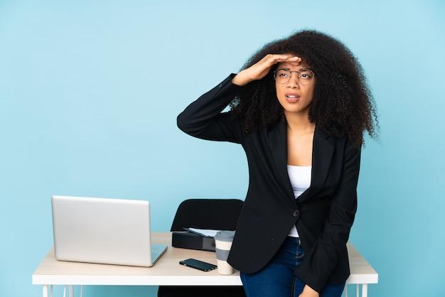 African american biznes kobieta pracuje w swoim miejscu pracy, patrząc daleko ręką, aby coś spojrzeć