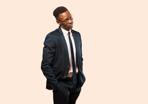 African american biznesmen szuka dumny, pewny siebie, fajny, bezczelny i arogancki, uśmiechnięty, czuje się udany na beżowej ścianie