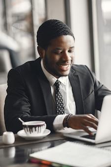 African american biznesmen za pomocą laptopa w kawiarni.