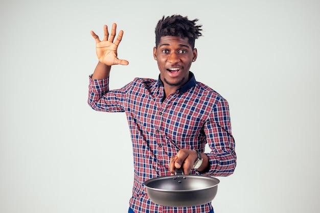 African american chef kitchener trzymający patelnię czarodziej człowiek gotujący magię latającą sałatkę z jedzeniem, marchew, czosnek, cebula, pieprz, ziemniaki, ogórek izolować białe tło studio.magic smaku fantazji.