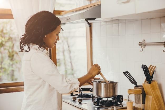 African american czarna kobieta gotowania wrzącej zupy w kuchni w domu.