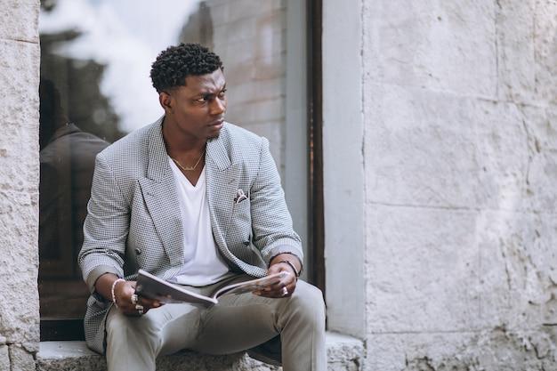 African american człowiek czytania magazynu