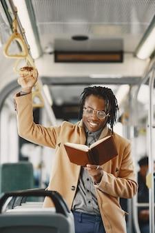 African american człowiek jedzie w autobusie miejskim. facet w brązowym płaszczu. człowiek z notatnikiem.