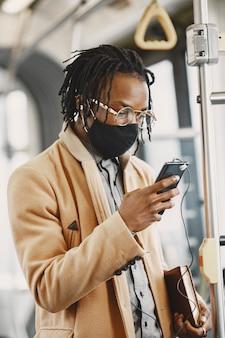 African american człowiek jedzie w autobusie miejskim. facet w brązowym płaszczu. koncepcja wirusa koronowego.