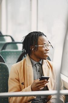 African american człowiek jedzie w autobusie miejskim. facet w brązowym płaszczu.