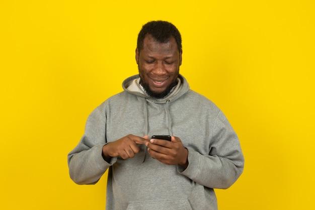 African american człowiek patrząc na coś przez telefon, stoi nad żółtą ścianą.