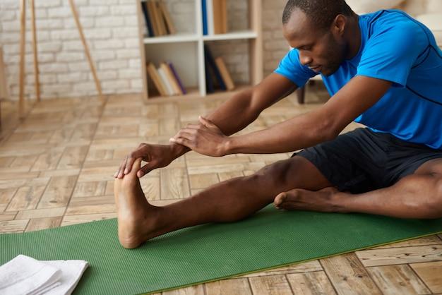 African american człowiek robi rozciąganie mięśni nóg.