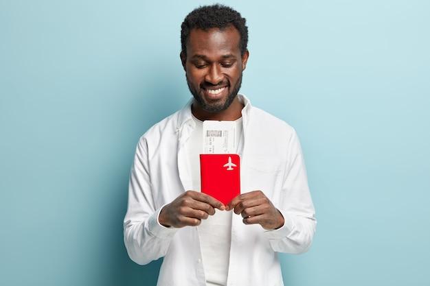 African american człowiek ubrany w białą koszulę, trzymając bilety lotnicze