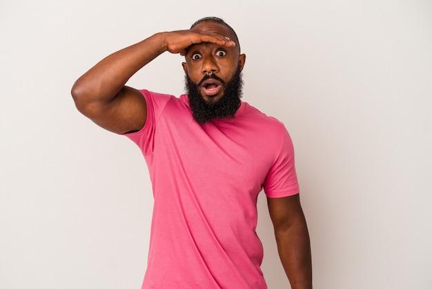 African american człowiek z brodą na białym tle na różowym tle patrząc daleko trzymając rękę na czole.