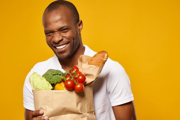 African american człowiek z papierową torbę ze śmiechem świeżej żywności