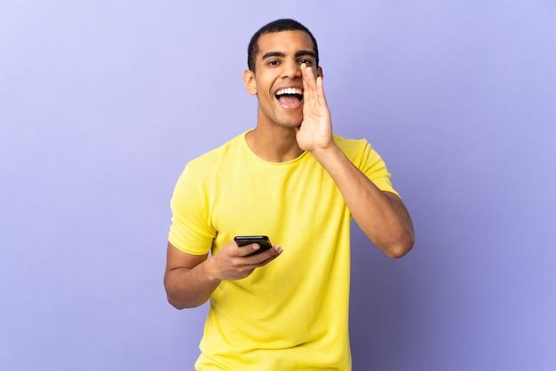 African american człowieka na pojedyncze fioletowe przy użyciu telefonu komórkowego krzycząc z szeroko otwartymi ustami