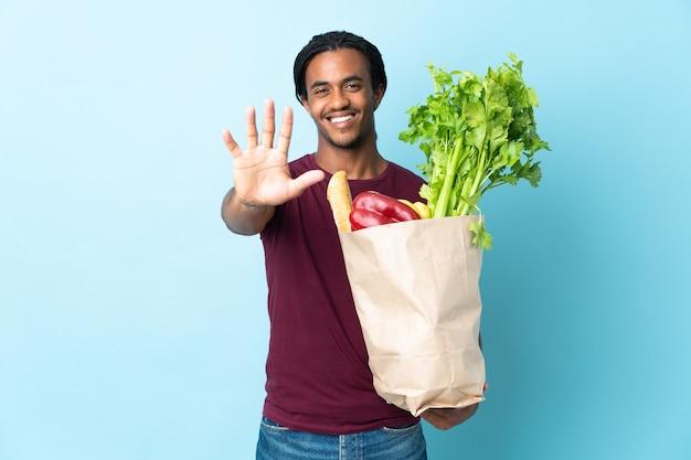 African american człowieka posiadającego torbę na zakupy spożywcze na białym tle na niebieskiej ścianie, licząc pięć palcami