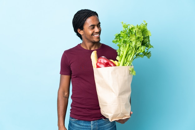 African american człowieka posiadającego torbę na zakupy spożywcze na białym tle na niebieskiej ścianie, patrząc z boku i uśmiechnięte