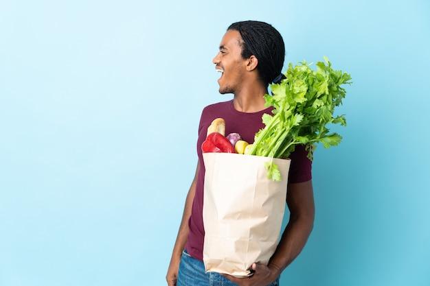 African american człowieka posiadającego torbę na zakupy spożywcze na białym tle na niebieskim tle, śmiejąc się w pozycji bocznej