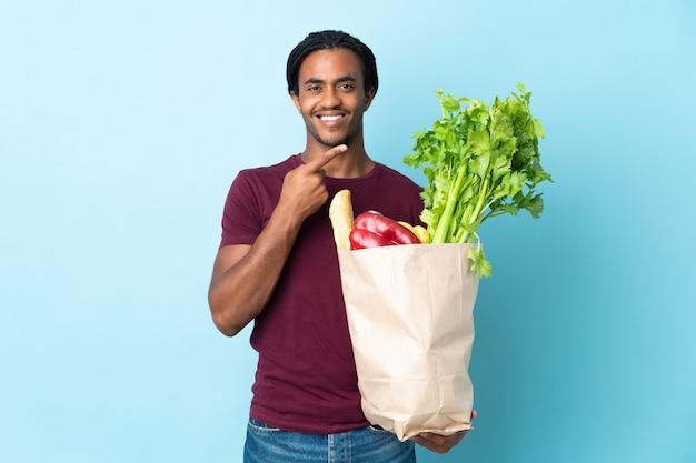 African american człowieka posiadającego torbę na zakupy spożywcze na białym tle na niebieskim tle, wskazując na bok do przedstawienia produktu