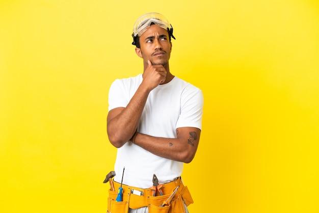 African american elektryk mężczyzna nad odosobnioną żółtą ścianą patrząc w górę podczas uśmiechania się