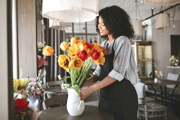 African american girl gospodarstwa wazon z kolorowymi kwiatami m? oda kwiaciarnia w fartuch tworzenie pi? knego bukiet