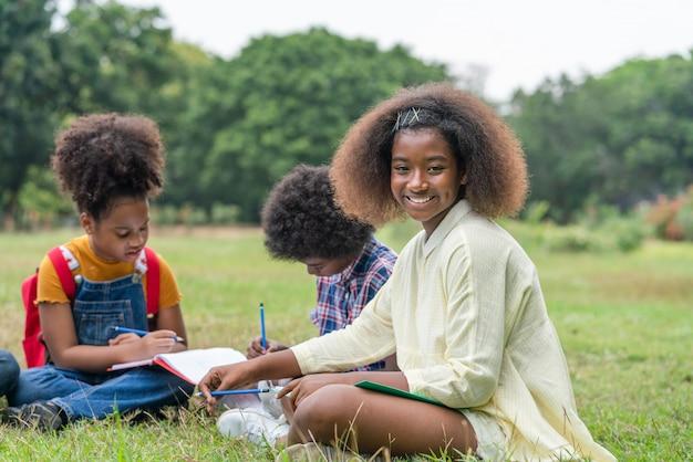 African american girl siedzi i odrabiania lekcji z przyjaciółmi w parku szkolnym. koncepcja edukacji zewnętrznej