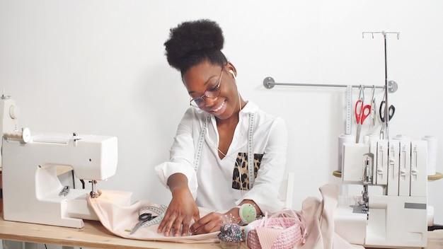 African american kobiet profesjonalny projektant mody pracuje na tkaninie w warsztacie
