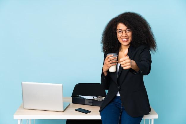 African american kobieta biznesu pracująca w swoim miejscu pracy z kciukami do góry, ponieważ stało się coś dobrego