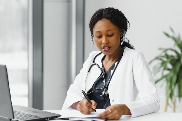 African american kobieta lekarz pracujący w swoim biurze w trybie online za pomocą przenośnego urządzenia informacyjnego