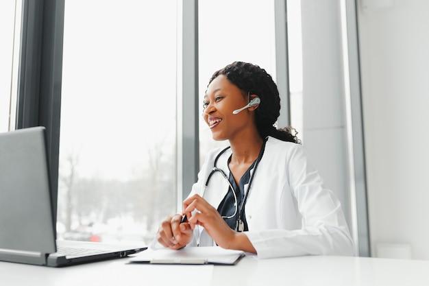 African american kobieta lekarz pracujący w swoim biurze w trybie online za pomocą przenośnego urządzenia informacyjnego.