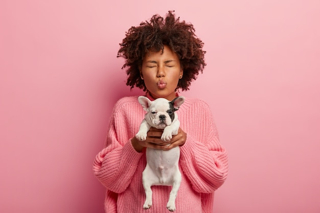 African american kobieta ma na sobie różowy sweter gospodarstwa szczeniaka