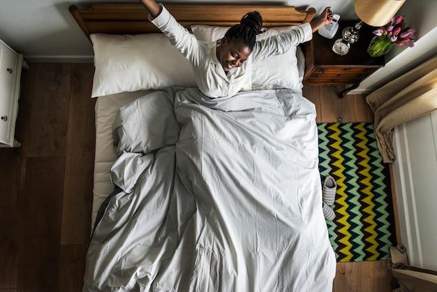 African american kobieta na łóżku budzi się rano