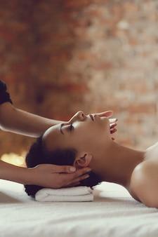 African american kobieta odbiera relaksujący masaż w spa