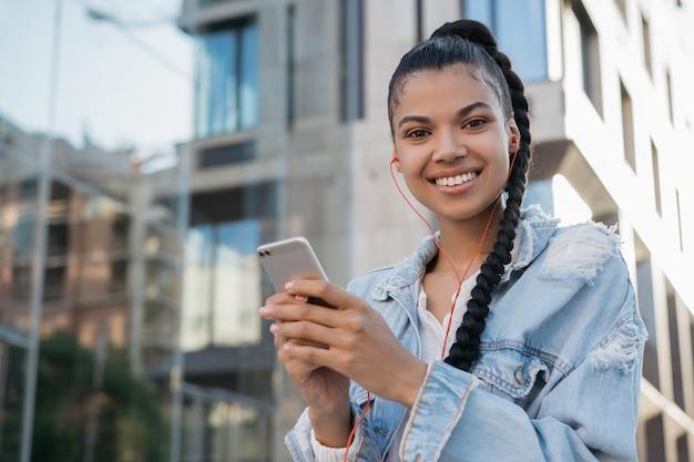 African american kobieta przy użyciu telefonu komórkowego, chodząc po ulicy, uśmiechając się