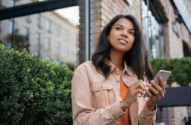 African american kobieta przy użyciu telefonu komórkowego, czekając na taksówkę na zewnątrz