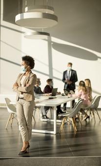 African american kobieta stojąca w biurze i nosząca maskę jako ochrona przed koronawirusem