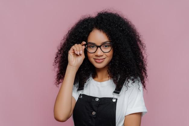 African american kobieta trzyma rękę na ramce okularów, uśmiecha się radośnie